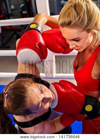 Two aggressive boxer women wearing boxer red gloves boxing in ring.
