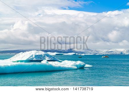 Iceberg and sightseeing boats in Jokulsarlon a glacial river lagoon in southeast Iceland
