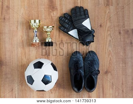 sport, achievement, championship and success concept - close up of soccer ball, football boots and goalkeeper gloves with golden cups on wooden background