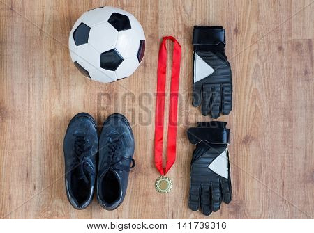 sport, achievement, championship and success concept - close up of soccer ball, football boots and goalkeeper gloves with golden medal on wooden background