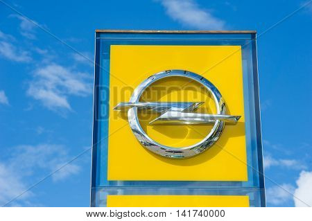 VILNIUS, LITHUANIA: AUGUST 7, 2016: Opel official dealership logo over blue sky. Adam Opel AG is a German automobile manufacturer and a subsidiary of the American General Motors Company.