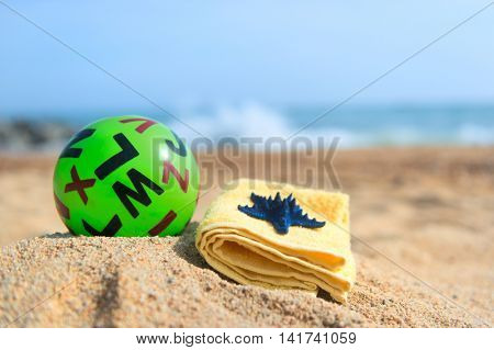 Green toy ball with letters and towel at the beach
