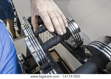 An image of a man grabbing a dumbbell