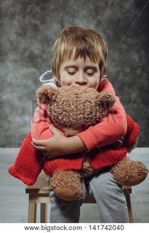 Boy 5 Years Old Hugging Big Teddy Bear Sits On A Chair