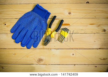 Tools and gloves on wooden table in vintage