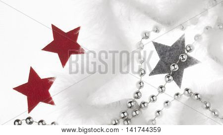 Beautiful Christmas and New Year decoration - red gray stars of warm felt the big star of the white fluff and silver beads on a white background isolated