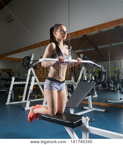 Female body builder doing arms exercises on machine in the gym