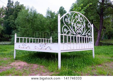Iron white bed on the river bank