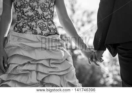 Close up on bride in fancy ruffled dress and groom holding hands in black and white.
