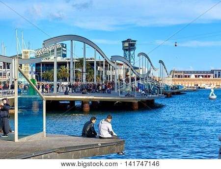 Barcelona Spain - April 3 2016: Crowd of people in the Rambla de Mar in Barcelona city. The Ramla del Mar is a main tourist attraction it has a leisure center shops restaurants IMAX cinema and an aquarium. Barcelona. Spain