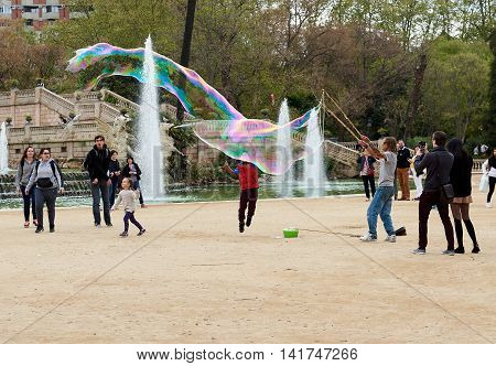Barcelona Spain - April 4 2016: People enjoy the soap bubbles in the in the Ciutadella Park in Barcelona. Ciutadella park is one of the finest parks in Barcelona. Park dotted with historic landmarks statues and fountains