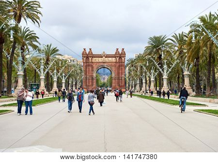 Barcelona Spain - April 4 2016: Day view to The Arc de Triomf. Crowd of people walking along the pedestrian street of the Passeig de Lluis Companys in Barcelona. The Arc de Triomf is one of the city's iconic and remarkable landmarks. Spain