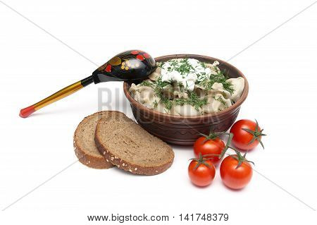 dumplings with meat in an earthenware bowl bread and tomatoes on a white background. horizontal photo.