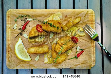 Fried fish in batter with herbs and lemon