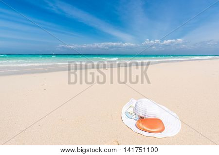 white hat, sunglasses and suntan cream on a seashore with blue ocean and sky on the background
