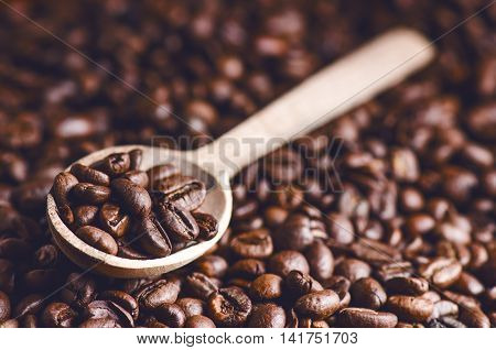 Spoon of coffee beans. Background. Energy. Raw coffee beans. Grained product. Hot drink. Close up. Harvesting. Natural background. Lifestyle. Coffee break in a morning. Wooden spoon.