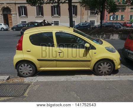 ROME ITALY - CIRCA JULY 2016: yellow Peugeot 107 parked in a street of the city centre