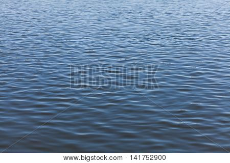 Wavy water surface of river with ripples abstract background