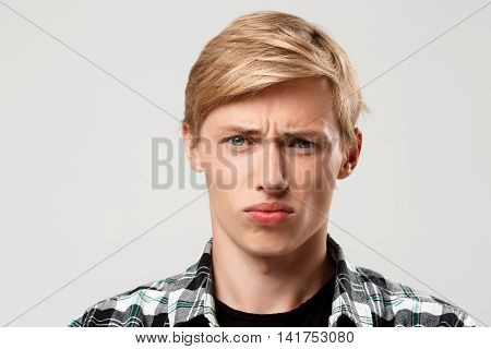 Close up portrait of handsome confident blond young man wearing casual plaid shirt looking in camera on grey background