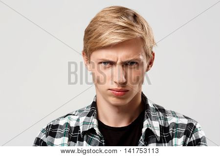 Close up portrait of handsome confident blond young man wearing casual plaid shirt looking in camera isolated on grey background