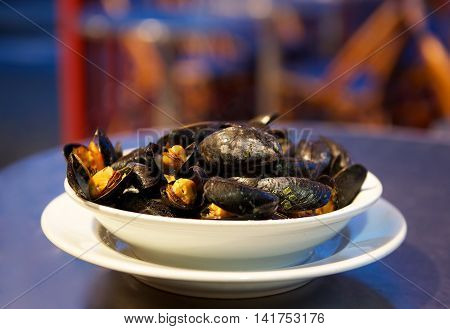 Steamed mussels in white wine sauce. Bowl of steamed mussels in white sauce in blurry violet background. French mussels. Traditional french meal