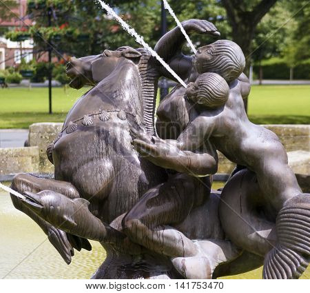 PORT SUNLIGHT, ENGLAND, JUNE 29. A pool and fountain on June 29, 2016, in Port Sunlight, England. A man and boy on a horse flanked by dolphins sprays water into a pool in Port Sunlight England.