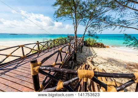 beautiful landscape with wooden pier leading to the clear blue ocean on Turtles Island, Zanzibar