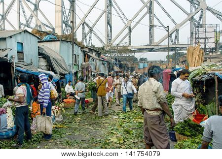 KOLKATA, INDIA - JAN 13, 2016: Buyers and traders of popular Mullik Ghat Flower Market on old indian street on January 13, 2016. More than 125 years old market has near 2000 sellers workers every day