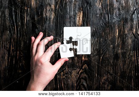 hand with missing piece of white jigsaw on dark wooden table