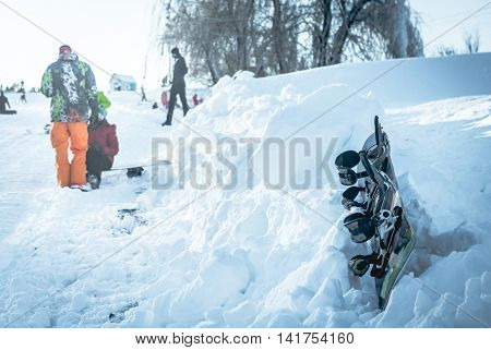 snowboard lying on snowdrift on the hillside with people on the background