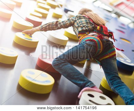 little girl climbing the wall in entertainment center