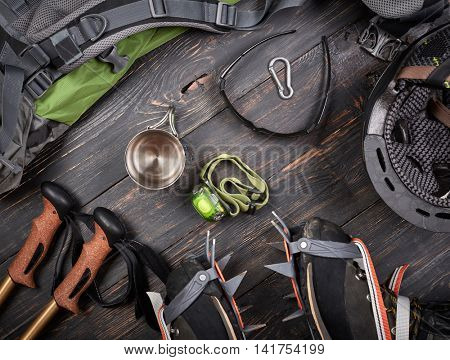 Climber accessories set on dark wooden background:  boots with crampon, backpack, sunglasses, flashlight and others. Top view