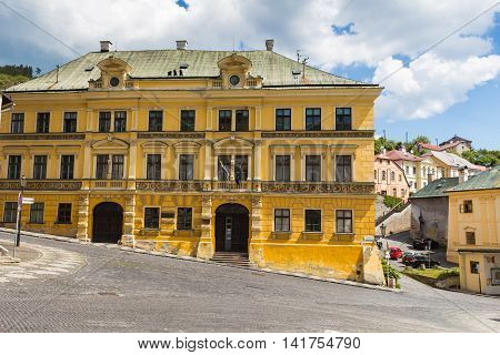 Yellow building called Fritz´s house on the City Hall Square in Banska Stiavnica Slovakia former mining city. Cloudy sky.
