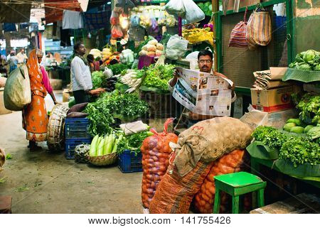 KOLKATA, INDIA - JAN 10, 2013: Marketplace with fresh grocery and poor customers of indian city on January 10, 2013. Only 081 perc. of the Kolkata's workforce employed in the primary sector -agriculture