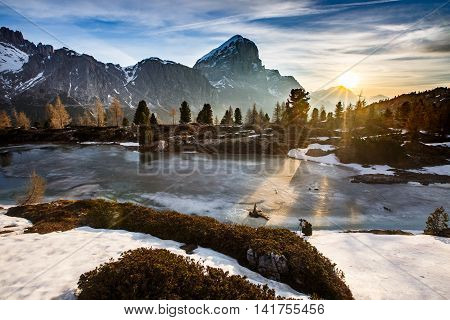 Winter mountain landscape with frozen lake in the front and dramatic sky of evening sun in the background sunrays protruding trees. Wilderness raw nature concept and background. Limides Dolomites.