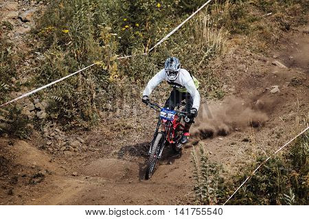 Magnitogorsk Russia - July 23 2016: young rider athlete on bicycle rides along a dusty trail during National championship downhill