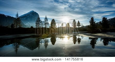 Mountain landscape with lake in the front and dramatic sunset evening sky above. Wilderness raw nature concept and background. Lago Limides Dolomites.