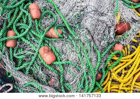 pile of fishing nets with floats and colorful nylon ropes
