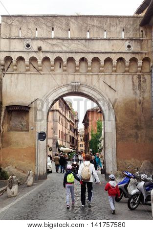 ROME, ITALY, MAY 26, 2013: a view of people wandering a roman street with an archway, cobblestone street, motor-bikes, and old buildings, in mid-afternoon