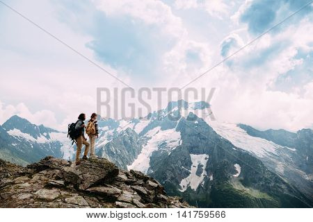 Father with child standing on the top of the mountain, winter hike with backpacks, alpine view