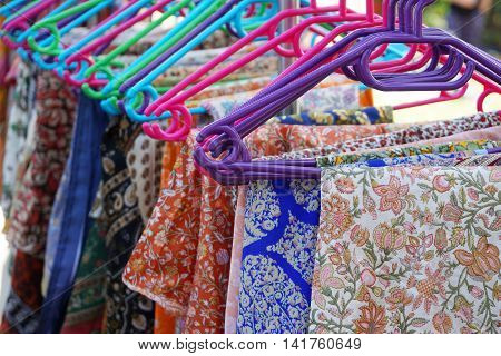 clothes rack with a selection floral pattern clothing on colorful hangers
