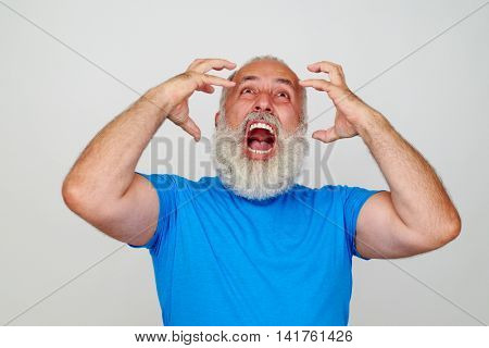 Stylish aged man with white beard is posing at the camera expressing anger isolated on blank white background