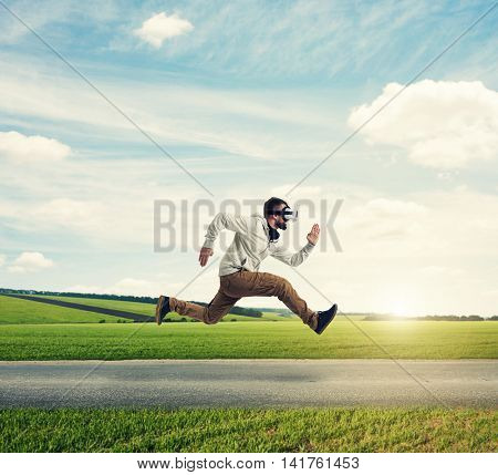 Young man in casual clothes and virtual reality headset is running violently on the background of green meadow during sunset