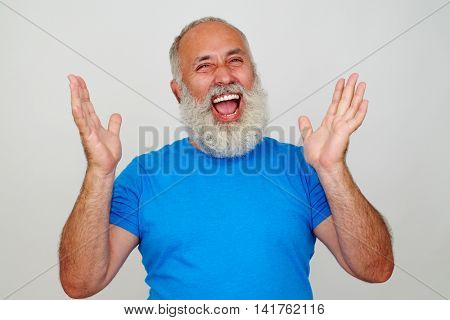 Aged stylish man in blue T-shirt is laughing sincerely with hands lifted isolated on white background