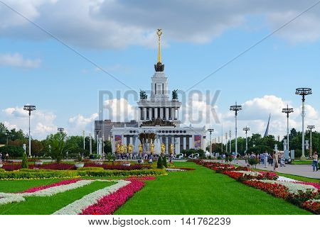 MOSCOW RUSSIA - JULY 23 2016: Unidentified people walk on Exhibition of Achievements National Economy near main pavilion and fountain