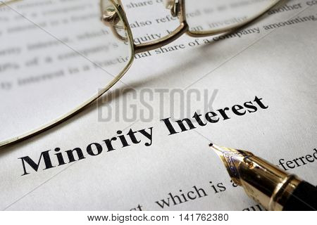 Sign minority interest on a paper and glasses.