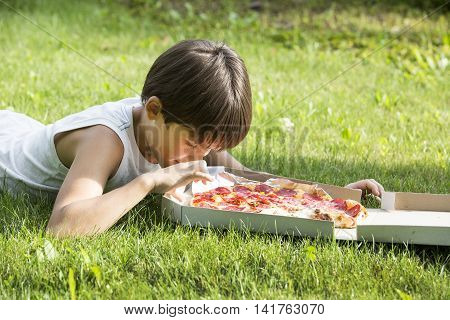boy eating pizza on the nature Appetite