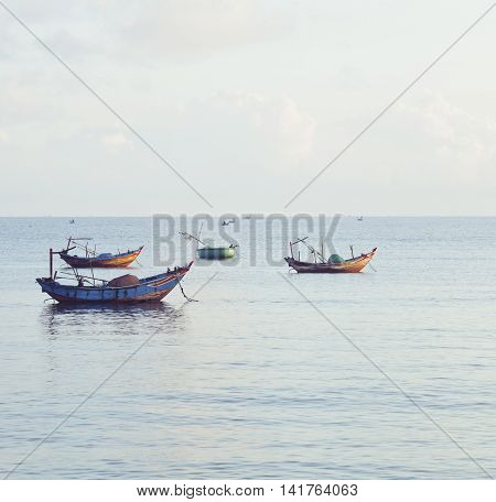 vietnameese national boats in sea at sunrise, blue clouds in harbour