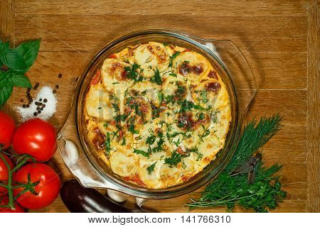 Vegetarian Moussaka. Traditional Greek dishes. Casserole with eggplants. Ingredients: aubergine potatoes tomatoes garlic egg yogurt onions nutmeg oregano. Transparent glass baking dish.