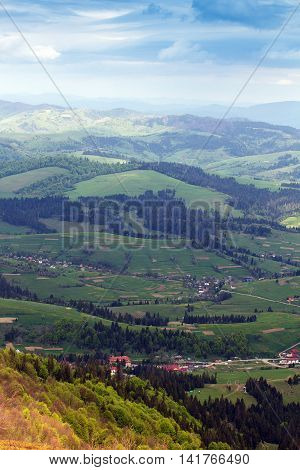 landscape consisting of a Carpathians mountains with fir-trees and green trees and grassy green valley with little houses and blue cloudly sky
